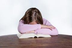 有书的睡觉的女孩在白色背景 免版税库存照片