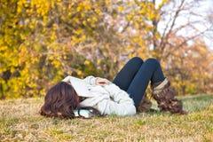 有书的美丽的女孩休眠在草的 库存图片