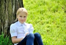 有书的美丽的小女孩在公园 免版税图库摄影