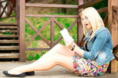 有书的美丽的少妇在公园 库存图片