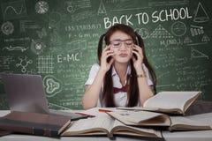 有书的迷茫的女小学生在类 免版税库存图片