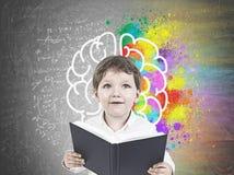 有书的逗人喜爱的小男孩,脑子 库存照片
