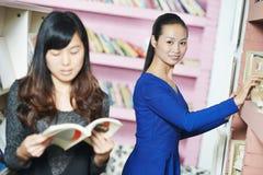有书的年轻中国学生女孩在图书馆里 免版税图库摄影