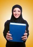 有书的年轻回教妇女在白色 免版税图库摄影