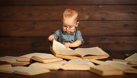 有书的滑稽的婴孩在玻璃 免版税库存照片