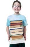 有书胳膊负荷的青少年的男孩  免版税库存图片