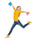 有书跳的愉快的学员女孩 免版税库存图片