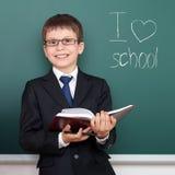 有书画象的男生在黑板背景,我爱学校课文,穿戴在经典黑衣服,教育概念 免版税库存照片