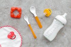 有乳奶和婴儿惯例的瓶搽粉了健康食物、玩具和围嘴在石背景顶视图 库存照片