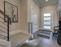 有乳脂状的墙壁和硬木地板的明亮的入口 免版税库存图片