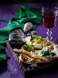 有乳酪、调味汁和红葡萄酒的几种类型的板材在紫罗兰色桌上 黑暗的口气,选择聚焦 免版税库存照片