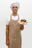 有乳酪盘子的男性厨师 库存照片