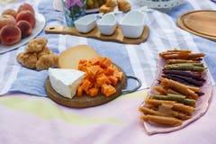 有乳酪assorti、pastillum卷和新月形面包布局的木盘子在蓝色野餐毯子 健康食品周末 免版税库存图片