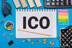 有事务的一个笔记本注意提供与办公室工具的最初的硬币ICO在蓝色背景 免版税库存照片