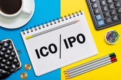 有事务的一个笔记本注意提供ICO对IPO原始股公开出售的最初的硬币与办公室工具 免版税库存图片