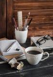 有事务的工作场所反对-书、笔记本、笔、片剂、玻璃和一杯咖啡和巧克力 免版税图库摄影
