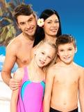 有二子项的愉快的家庭热带海滩的 免版税库存照片