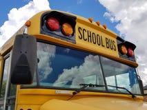 有云彩反射的黄色校车 库存图片