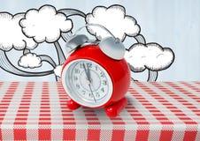 有云彩图画的时钟在红色桌布 免版税库存图片