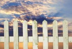 有云彩的白色尖桩篱栅 库存照片