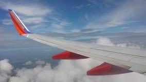 有云彩的飞机翼在蓝天下 免版税图库摄影