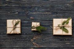 有云杉的分支的三个葡萄酒礼物盒在木背景 库存图片