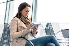 有互联网片剂的女实业家在机场。 免版税图库摄影
