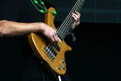 有五串低音吉他的低音演奏员手 免版税库存图片