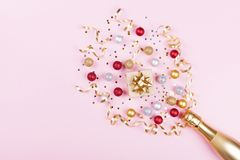 有五彩纸屑星、礼物盒和假日球的香宾瓶在粉红彩笔背景 圣诞节模式 平的位置样式 免版税库存照片