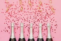 有五彩纸屑星的五个香宾瓶和在桃红色背景的党飘带 拷贝空间,顶视图 党背景 免版税库存图片