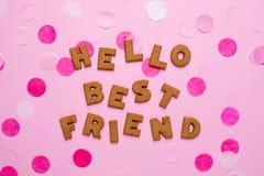 有五彩纸屑的信件曲奇饼Helllo最好的朋友在桃红色背景 免版税库存图片