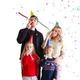 有五彩纸屑的家庭吹的党喇叭 免版税库存图片