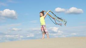 有五颜六色的丝带的小女孩在海滩 影视素材