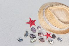 有五颜六色的丝带的葡萄酒夏天柳条草帽在与装饰石头和红海星的海滩 免版税库存照片