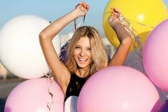 有五颜六色的乳汁气球的愉快的少妇 库存照片