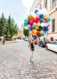 有五颜六色的乳汁气球的年轻白肤金发的妇女 免版税库存照片