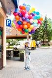 有五颜六色的乳汁气球的年轻白肤金发的妇女 免版税库存图片
