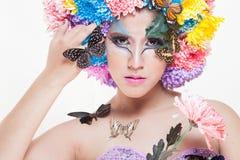 有五颜六色的亚裔美丽的女孩用新鲜的菊花花和蝴蝶组成 免版税库存图片