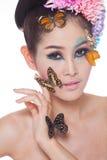 有五颜六色的亚裔美丽的女孩用鲜花和蝴蝶组成 库存图片