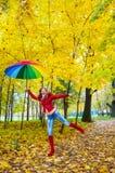 有五颜六色的伞的俏丽的女孩在秋天公园 免版税库存图片