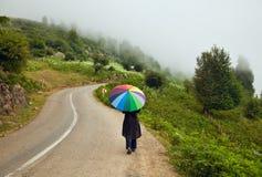 有五颜六色的伞的妇女步行沿着向下一个有雾的弯曲道路的 免版税库存照片