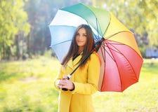 有五颜六色的伞的,俏丽女孩摆在美丽的妇女 免版税图库摄影
