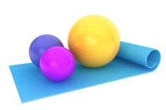 有五颜六色的健身球的锻炼席子 图库摄影