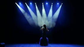 有五颜六色的光的少妇在音乐会唱歌 股票视频