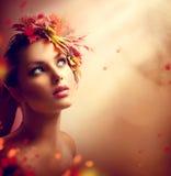 有五颜六色的叶子的浪漫秋天女孩 免版税图库摄影