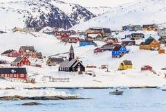 有五颜六色的因纽特人房子的北极解决岩石小山的 库存图片