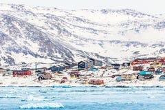 有五颜六色的因纽特人房子的北极雪城市全景岩石的 库存图片