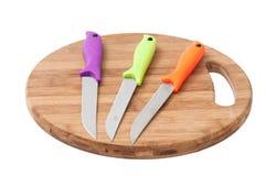有五颜六色的塑料把柄的厨刀在一个木板 免版税库存照片