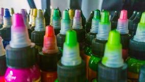 有五颜六色的墨水的多个瓶纹身花刺的 侧视图 特写镜头 免版税库存照片