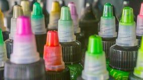 有五颜六色的墨水的多个瓶纹身花刺的 侧视图 特写镜头 图库摄影